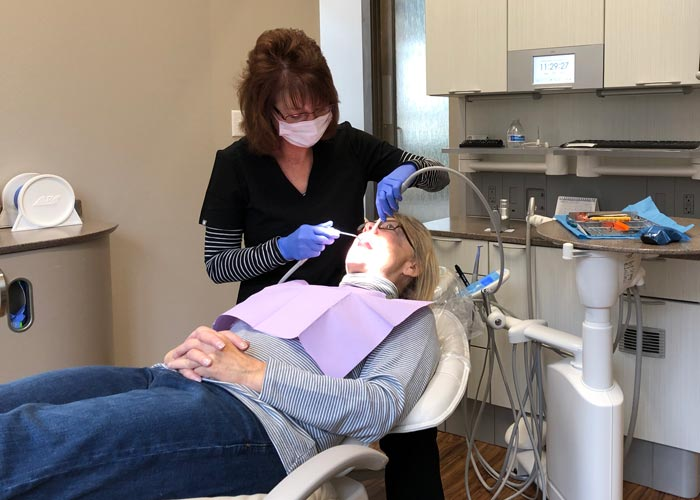Dental assistant cleaning teeth at Dr. Daves Dental office in west des moines